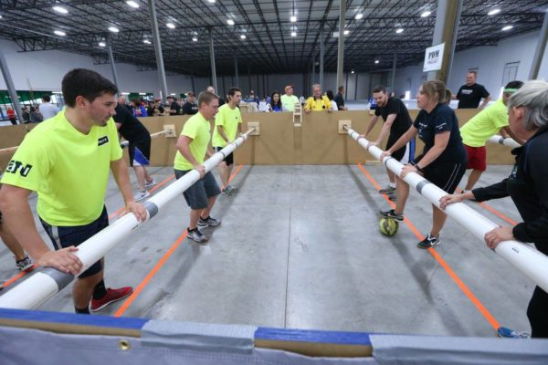 Two teams facing each other playing human foosball